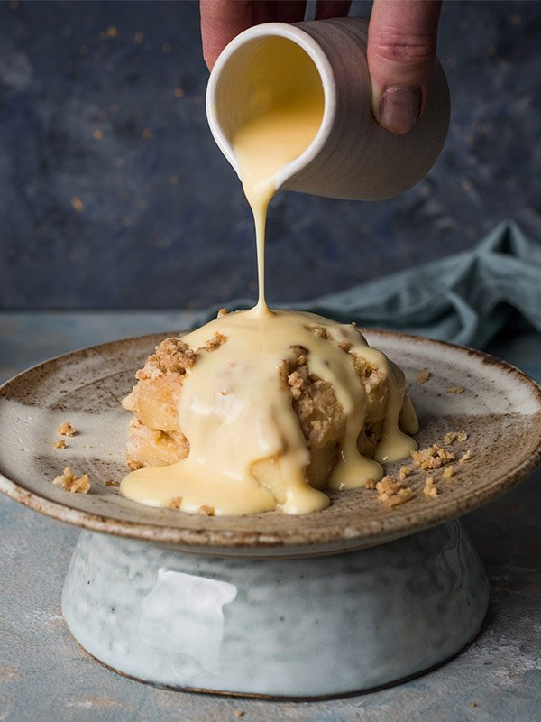 pouring custard over slab apple crumble